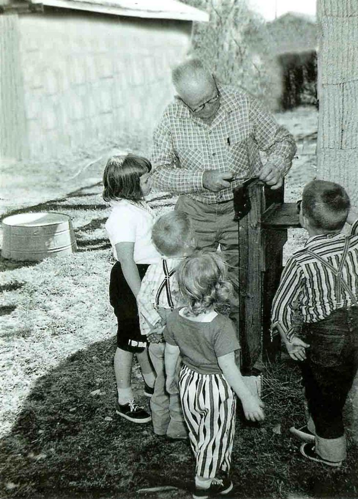 My grandfather sharpening a saw as grandchildren look on.  I'm second from the left.