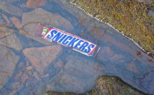 Snickers bar cooling in a small stream.