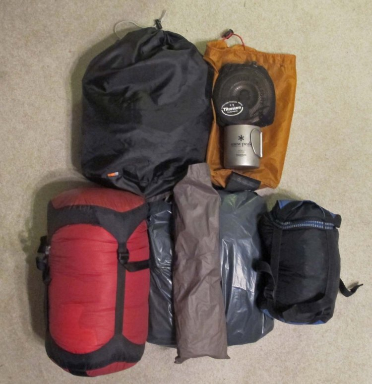 L to R top: Food bag, cook pot, Esbit stove, cup L to R bottom: sleeping bag, mattress, tent poles and tent.