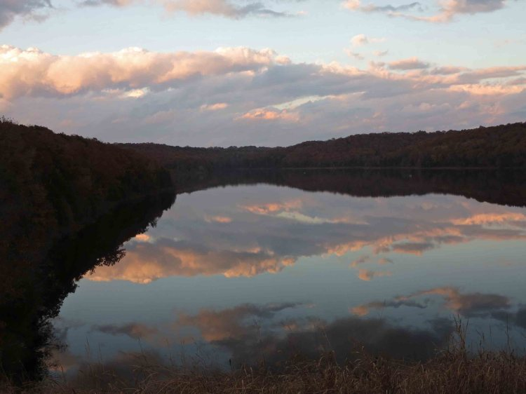 """Continuing to view the """"convergence,"""" the clouds moved into a symmetrical form on an axis formed by the land on the far side of the lake."""