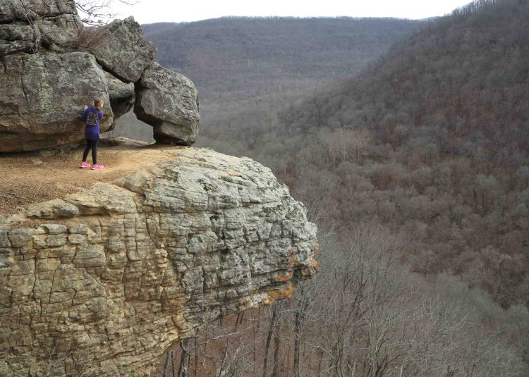 Young hiker taking in the views and staying away from the edge.