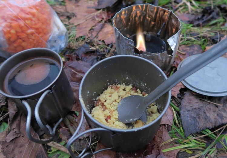 Coffee and Eggs prepared on a small camping stove in the woods.