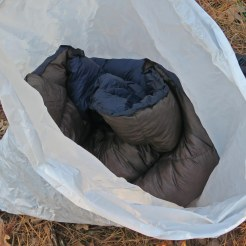 Down quilt and extra clothes in trash compactor bag