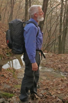 Experienced hiker carrying a 14lb backpack looking around the woods.