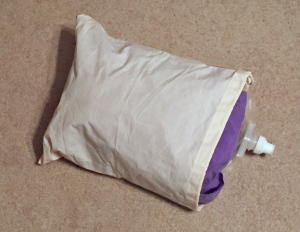 A purple platypus water pouch filled with air in a pillowcase.